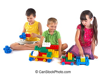 Playing children with constructing sets and toys