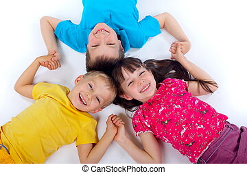 Happy Children - Children lying on backs and liking arms...