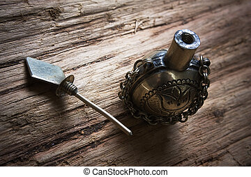old metal vials for potions on a wooden board
