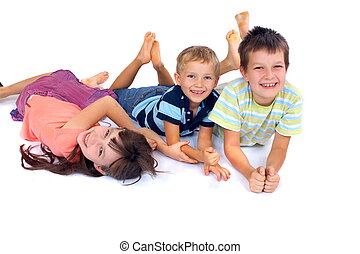 Smiling Children - Three children laying on the floor,...
