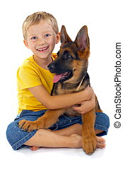 Smiling Boy With Dog - Smiling young blond boy sitting in a...