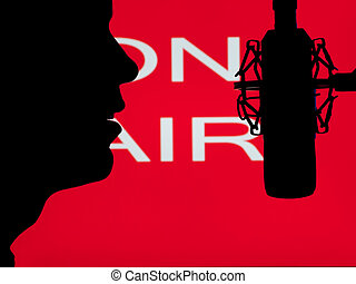 man speaking into the microphone with on the air sign in the...