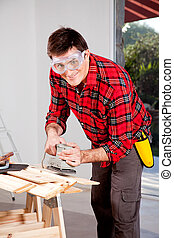 Hand Sander - A man wearing saftey goggles using an electric...