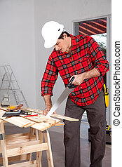 Hand Saw Wood Working - A wood worker using a hand saw in a...