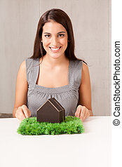 Happy House Woman - A woman holding a model house which is...