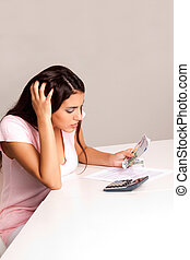 Woman Budget Money - A worried woman counting money and...