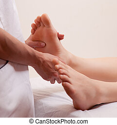 Foot Massage Detail - A close-up detail of a masseur giving...