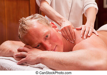 Man Receiving a Massage - A detail of a man receiving a back...