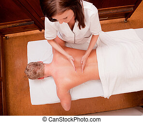 Percussive Massage - A man receiving a percussive back...