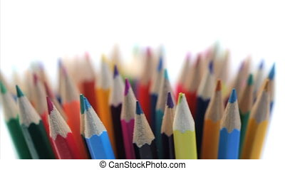 Several color pencils rotating on a white background