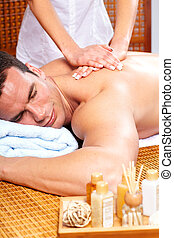 spa massage - handsome young man getting spa massage. Relax.