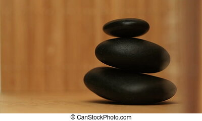 Pile of black pebbles rotating - Black pebbles rotating on a...