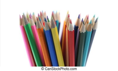 Color pencils rotating in a pencil holder on a white...
