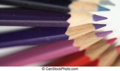 Top of color pencils turning on a white background