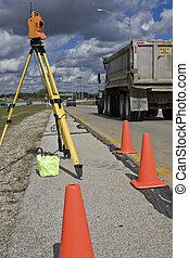 Survey on the highway - orange theodolite and semi-truck