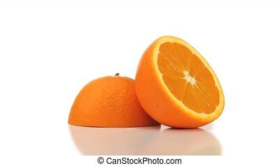 Two halves of an orange turning on a white background