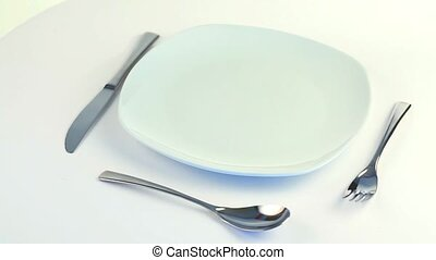 Plate, fork, knife and spoon turning on a white background