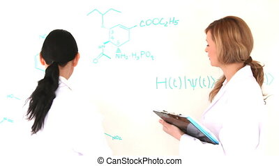 Scientist women writing a formula on a whiteboard in a...
