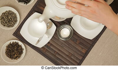 Woman pouring tea into cups from te