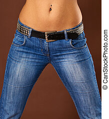 Young woman in jeans - close-up belly and hips