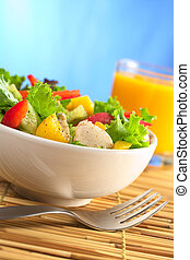 Fresh and healthy chicken salad with lettuce, mango, red bell pepper and cucumber with fresh juice in the back in front of blue background (Selective Focus, Focus on the front of the salad)
