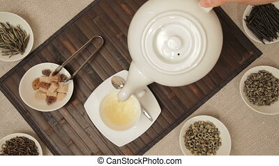 Woman pouring tea into cup from tea - Woman pours green tea...