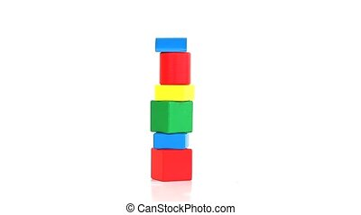 Tower of childrens coloured bricks rotating on a white...