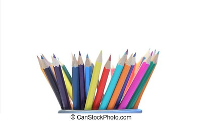 Color pencils in a pencil holder turning on a white...