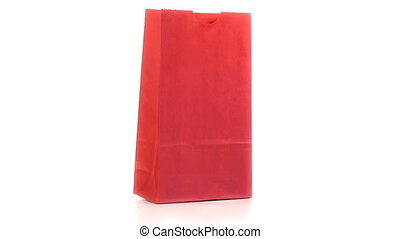 Red shopping bag turning on itself on a white background