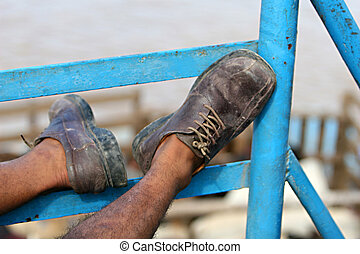 Take a Load Off - A man puts his feet up on a blue railing...