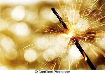 sparkler on bokeh background - sparkler on gold bokeh...