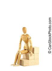 Wooden manikin sitting on blocks