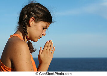 child praying outdoors