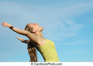 young woman shouting or singing arms raised with faith and...