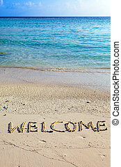 Word quot; welcome quot; is written on sand on oceanside -...