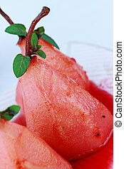 Pears Poached in Red Wine - A group of three pears that have...