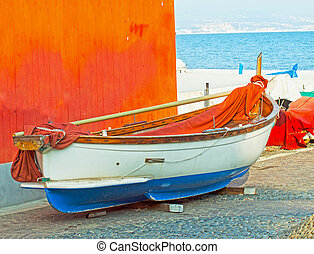 Boat near an orange wall, in a sea town