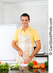 young man chopping vegetables - happy young man chopping...