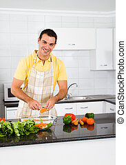 young man cutting vegetables - happy young man cutting...