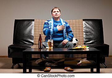 soccer fan on sofa - soccer fan is sitting on sofa and...