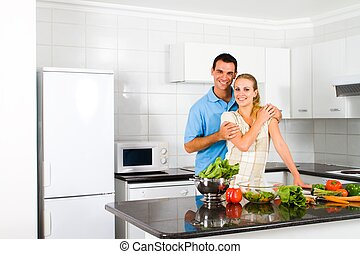 newlywed couple in home kitchen - young newlywed couple in...
