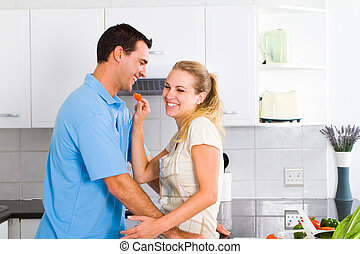 playful young couple tasting food