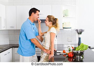 husband tasting food in kitchen