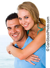 couple piggyback - happy young couple piggyback with...