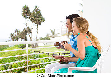 young couple sitting on balcony - happy young couple sitting...