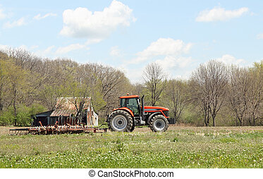 Tractor and Plow - Red tractor pulling a plow in a farm...