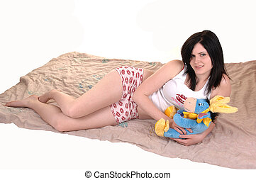 Girl in nightwear - A young pretty woman lying on her...