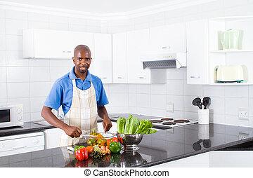 african man making salad