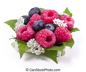 Ripe raspberry and blueberries with green leaf on white...