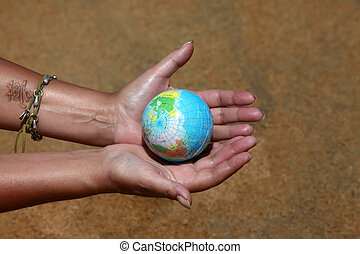 Saving world - Female hands with the small globe on a...